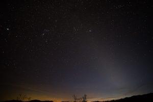 Star-strewn dark blue sky, yellow light on horizon, faint lighter band stretching up diagonally from bottom right.