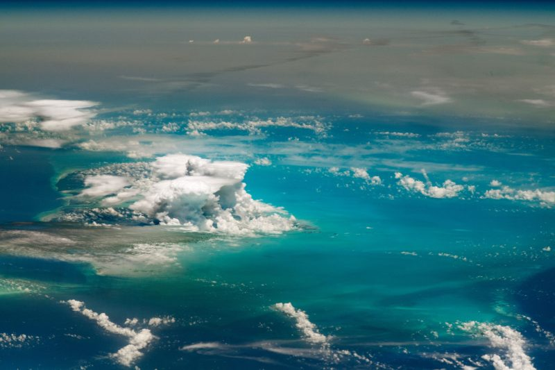 Clouds seen from orbit floating over an expanse of blue and brown.