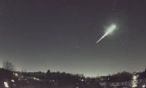 A streak of white, apparently exploding on the upper end, in a dark sky over trees.