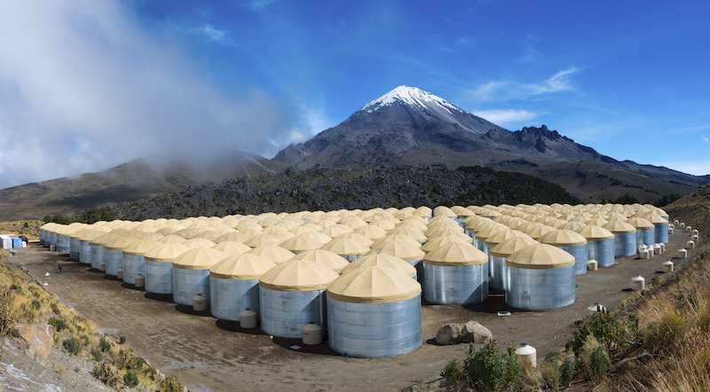 Large number of metal cylinders with tan conical tops, in front of black snow-capped mountain.