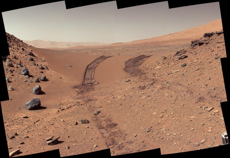 A rocky, red desert landscape, looking back along rover tracks to a distant rugged hill horizon.