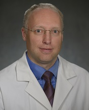 Man with gray hair and glasses in white lab coat.