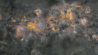 Dense star field with yellowish white and blue swirls and clouds.