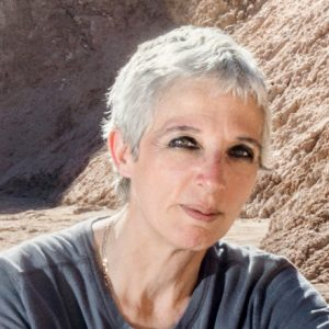 Woman with short silver hair and black eye makeup outside among reddish rocky hills.