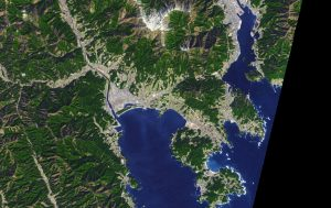 Satellite image of city on bay in Japan with no damage.