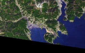 Satellite image of water encroaching city and floating debris.