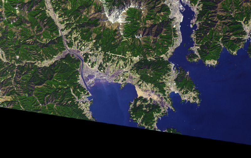 Satellite image of water encroaching city and yellow patches of floating debris.