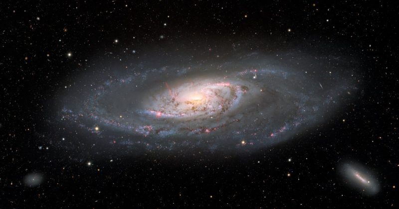 Large galaxy with spiral patterns around its bright center, with two much smaller, fainter galaxies nearby.