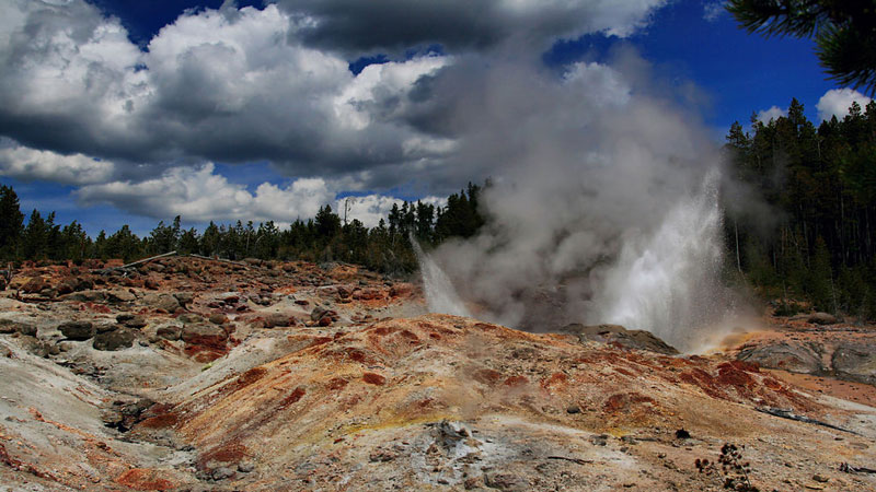 Lumpy multicolored mineral landscape with small billow of steam emerging from ground.