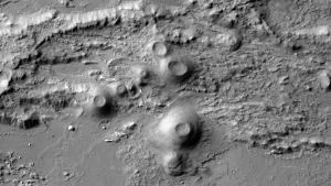 Black-and-white orbital view of small conical volcanoes in rough landscape.