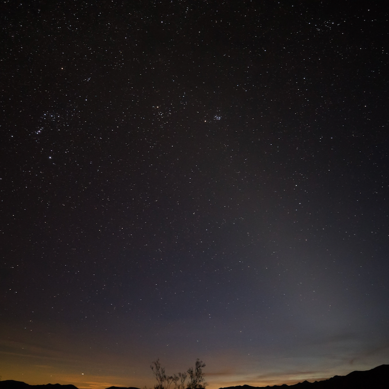 A starry sky over a desert landscape, and a faint cone of hazy light extending from the horizon.