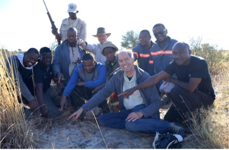 Group of 10 people pointing at a small rock.