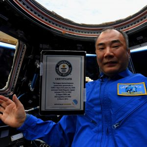 Man in blue with floating plaque in front of him.
