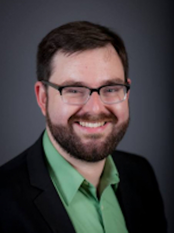 Smiling man with eyeglasses and beard and green shirt.