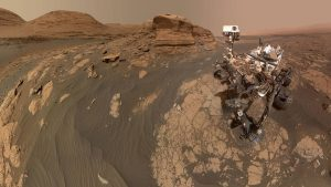 Robotic rover next to reddish buttes and mesas.