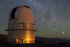 Dense star field with Milky Way and several bright stars behind a domed observatory building.