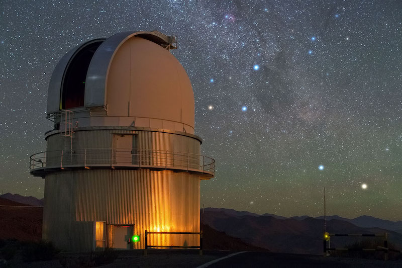 A telescope dome at in the foreground with Milky Way and bright stars in the sky.