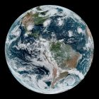 Western Hemisphere from space with land in green and brown, and blue oceans with white clouds.