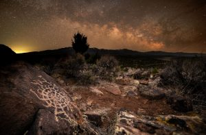 Orange-tinted starry clouds with rock etching in foreground.