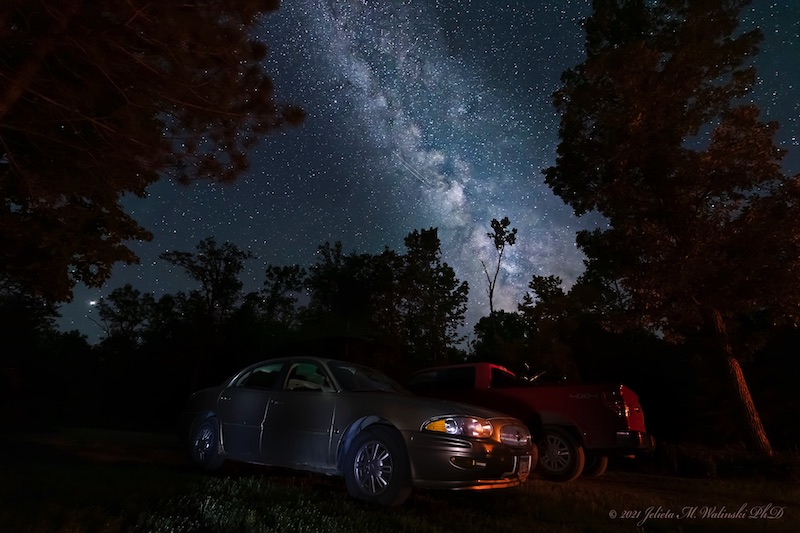 A dark blue night sky is dotted with white stars. Two cars are pictured beneath it. Lights and shadows in the sky make the Milky Way's spiral arm apparent.