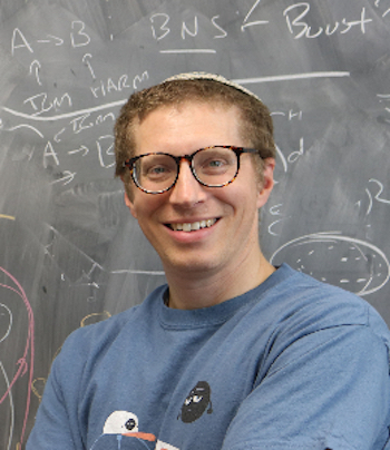Smiling man with eyeglasses in front of chalkboard.