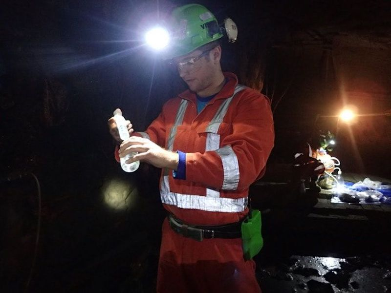 A dark mine with a man in an orange coverall and with a brilliant light on his helmet.