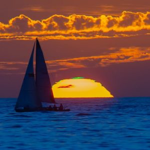 Sailboat in solhouette in front of a setting sun. The sun has a top layer of green.
