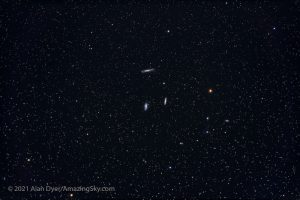 A star field with three small galaxies in the center.