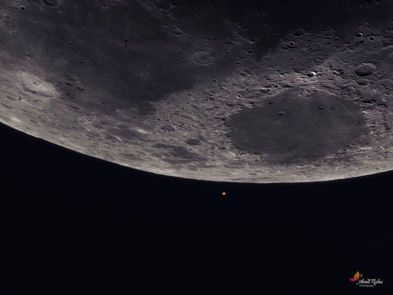 Closeup of moon's limb with red circle below.