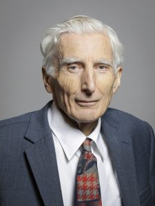 Elderly man with white hair in suit and tie.