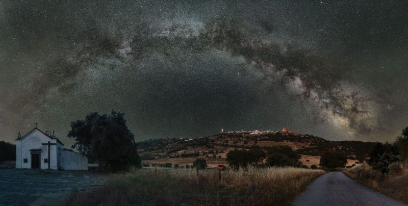 Wide shot of arching cloud of stars over countryside church.