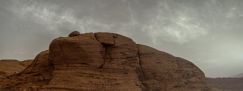 Reddish, rounded, rock outcrop with rock bump on top and white wispy clouds in sky above.