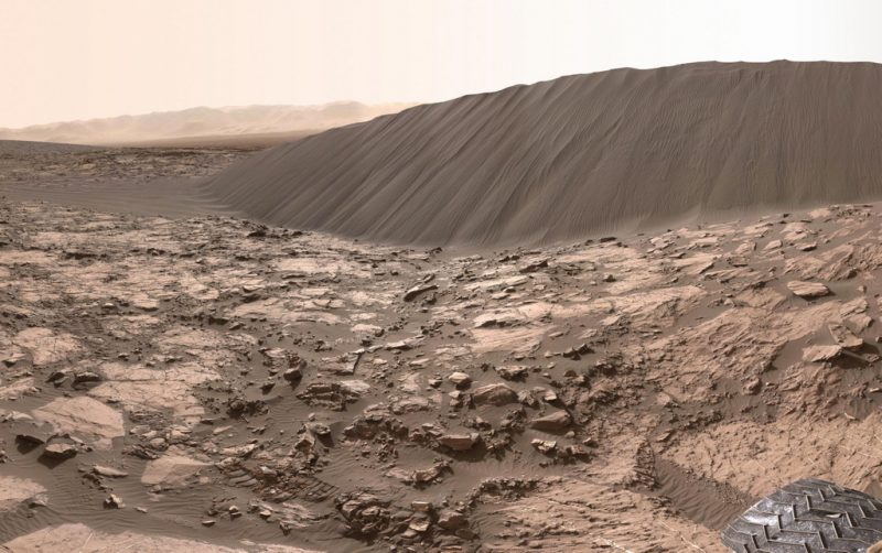 Large sand dune in rocky terrain with hills in background.