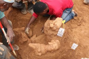 An archaeologist bends over a hole in the ground where terracotta figurines are being uncovered.