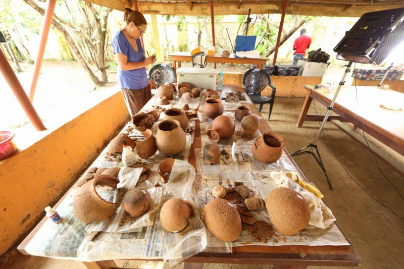 A table lined with newspaper, with pottery on top ranging from mostly intact vessels to shards. In the upper left corner, a female scientist is looking over her notes.