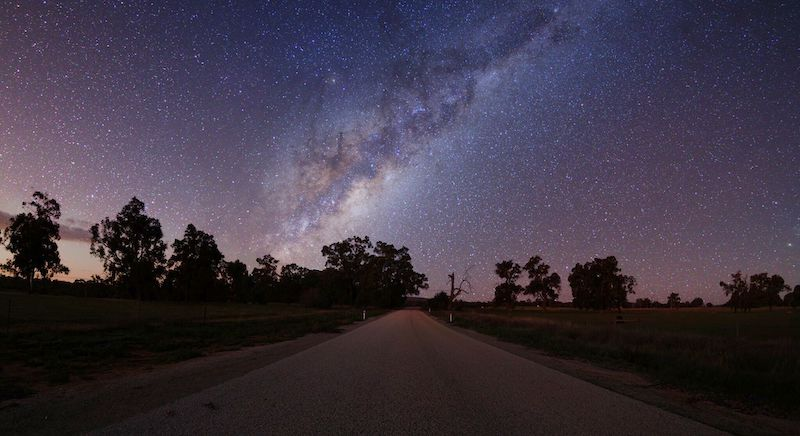 A purple night sky is dotted with white stars above a gravel road. Lights and shadows in the sky make the Milky Way's spiral arm apparent.