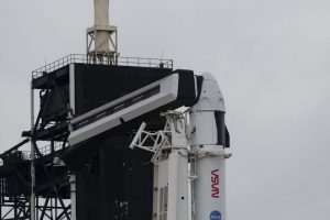 Blunt-nosed space capsule on top of cylindrical rocket next to gantry under cloudy sky.