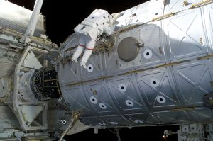 Astronaut floating beside a large metal tank in space.