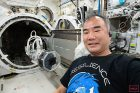 Asian man in black tee shirt, inside a space vehicle.