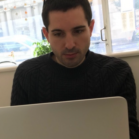 A young man in a simple black sweater, peering intently into his computer.