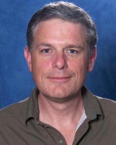 Man in gray collared shirt looking at camera.