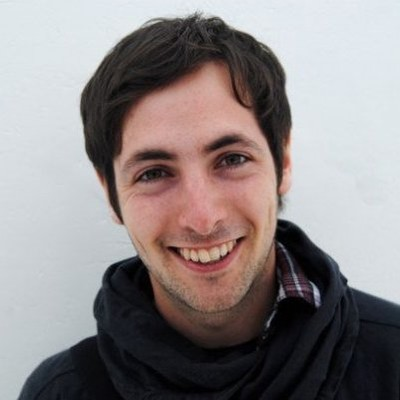 Smiling dark-haired young man with dark hoodie sweatshirt.