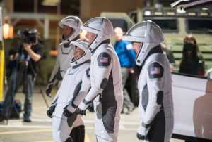 Four astronauts in space suits, walking together and laughing.