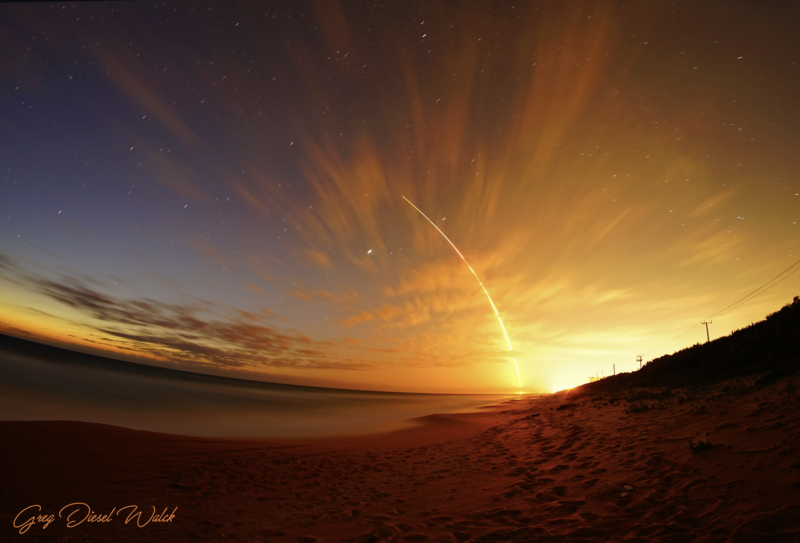 A distant shot of the brightly glowing arc of a launching rocket, against orange-pink dawn clouds.