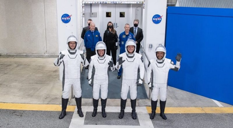 Four space-suited astronauts, in a line, smiling, one waving.