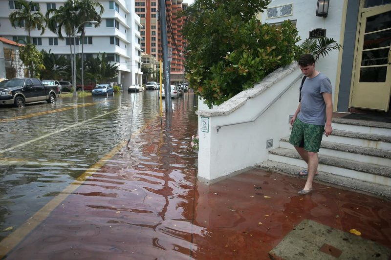 A man wearing flipflops steps onto a flooded sidewalk while leaving a hotel.
