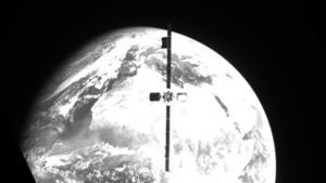 A satellite is pictured in grayscale, floating in space with Earth in the background.