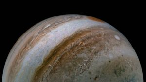 A view of half of Jupiter with bands, swirls, and ovals in tan to russet colors.