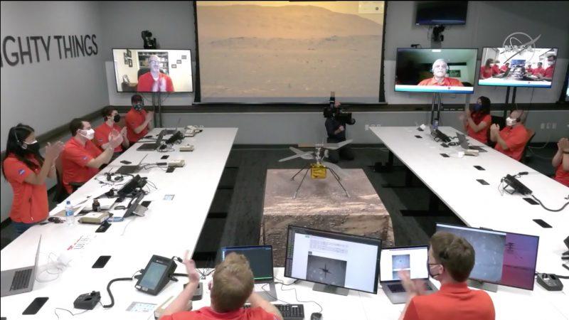 Chuyến bay trực thăng trên sao Hỏa đầu tiên, được nhìn thấy từ phòng điều khiển NASA / JPL, với bộ đồ màu đỏ táo bạo ngồi xung quanh chiếc bàn hình chữ U, với nhiều màn hình và một chiếc trực thăng mô hình ở trung tâm.
