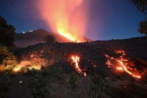 Fiery orange lighting up night sky above a mountain, lava streaking down the side.